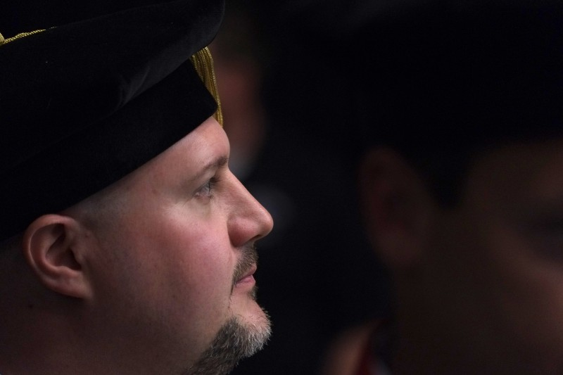 A graduate watches the procession into the 2013 Gardner-Webb University Commencement.