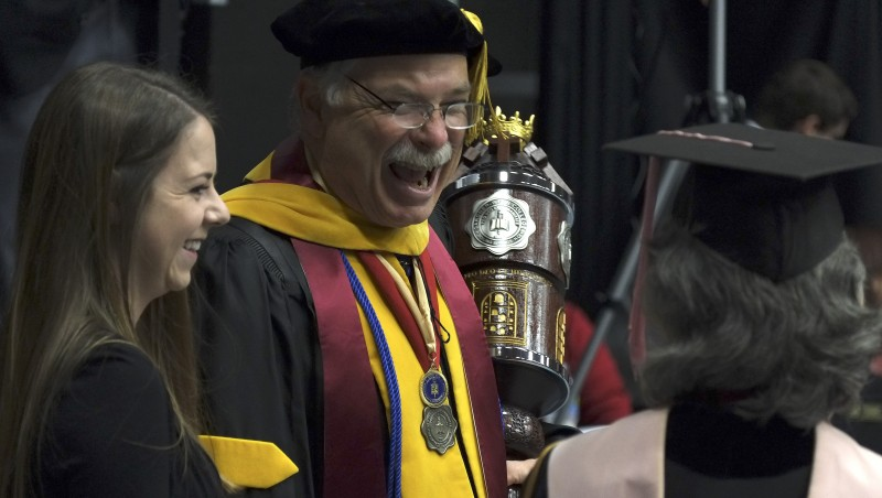 Dr. Tom Jones of the Natural Science Department prepares to lead the procession with the official mace.