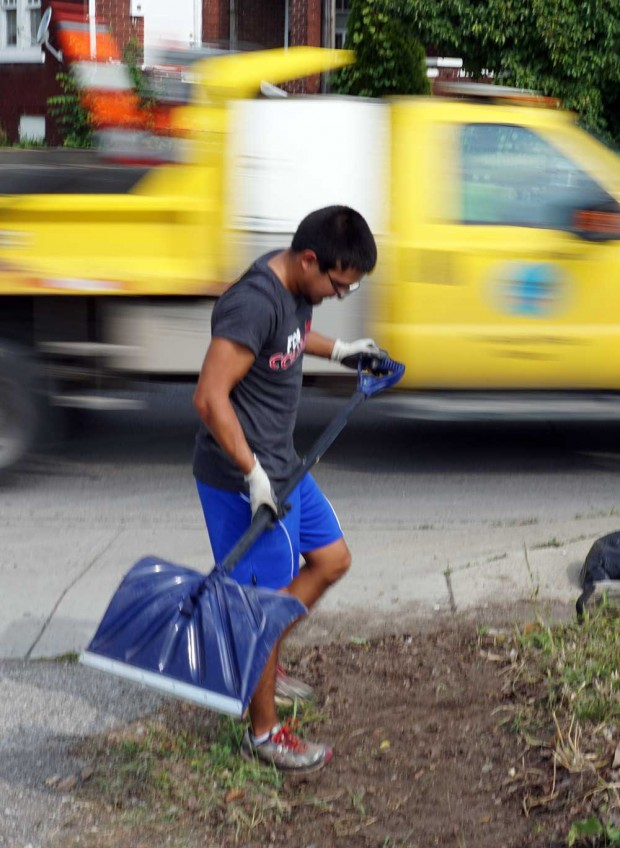 Quinton Englebright, a junior at the University of West Florida cleans dirt off the sidewalk on Cleveland Avenue in the Linden district of Columbus, Ohio, in cooperation with the Greater Linden Development Corporation.  ©2015 Bob Carey
