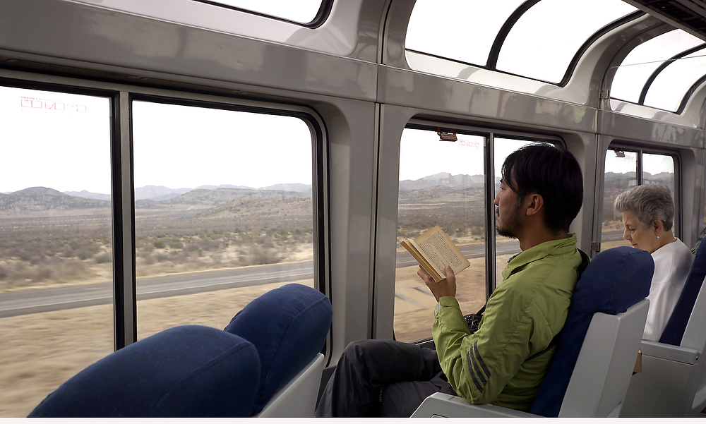 Noritoshi Ikezawa, a Japanese photographer reads as the Sunset Limited rolls through the West Texas desert. ©2015 Bob Carey (Sony a6000, Sony 24mm – 1/60, f8, iso 200)