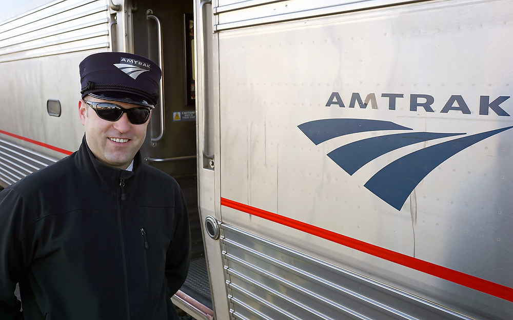 Amtrak assistant conductor Sheridan, a fourth generation rail worker greets passengers at the Klamath Falls station. ©2015 Bob Carey (Sony a6000, Sony 24mm – 1/125, f5, iso 125)
